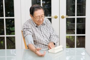 A senior Asian man using the blood pressure monitoring equipment. Retired, elderly Chinese man seated at a table in his home interior, using device for healthcare and medicine to stay healthy and aware.